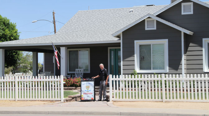 Councilmember Ken Remley poses in front of the home of the first recipient of the District 4 Home Beautification Award