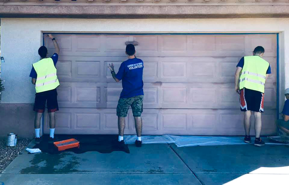 Volunteers help paint a garage door during the Surprise Day of Service event.
