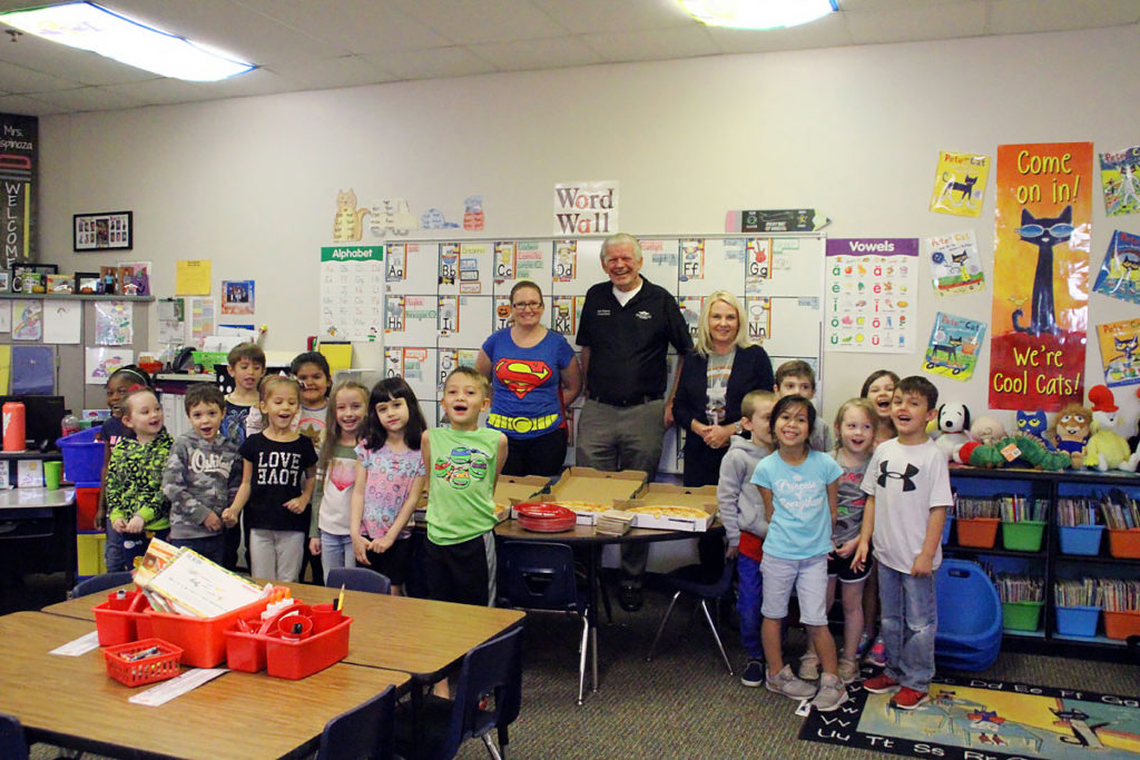 Councilmember Remley presents pizzas to an elementary school class.