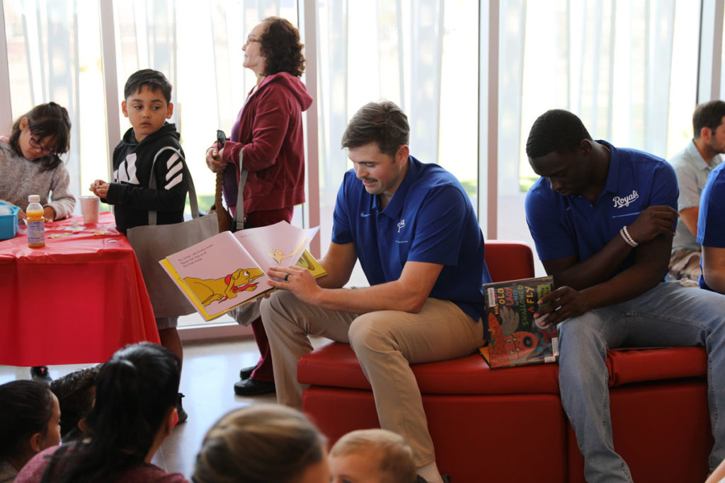 Kansas City Royals players read to children at the library.