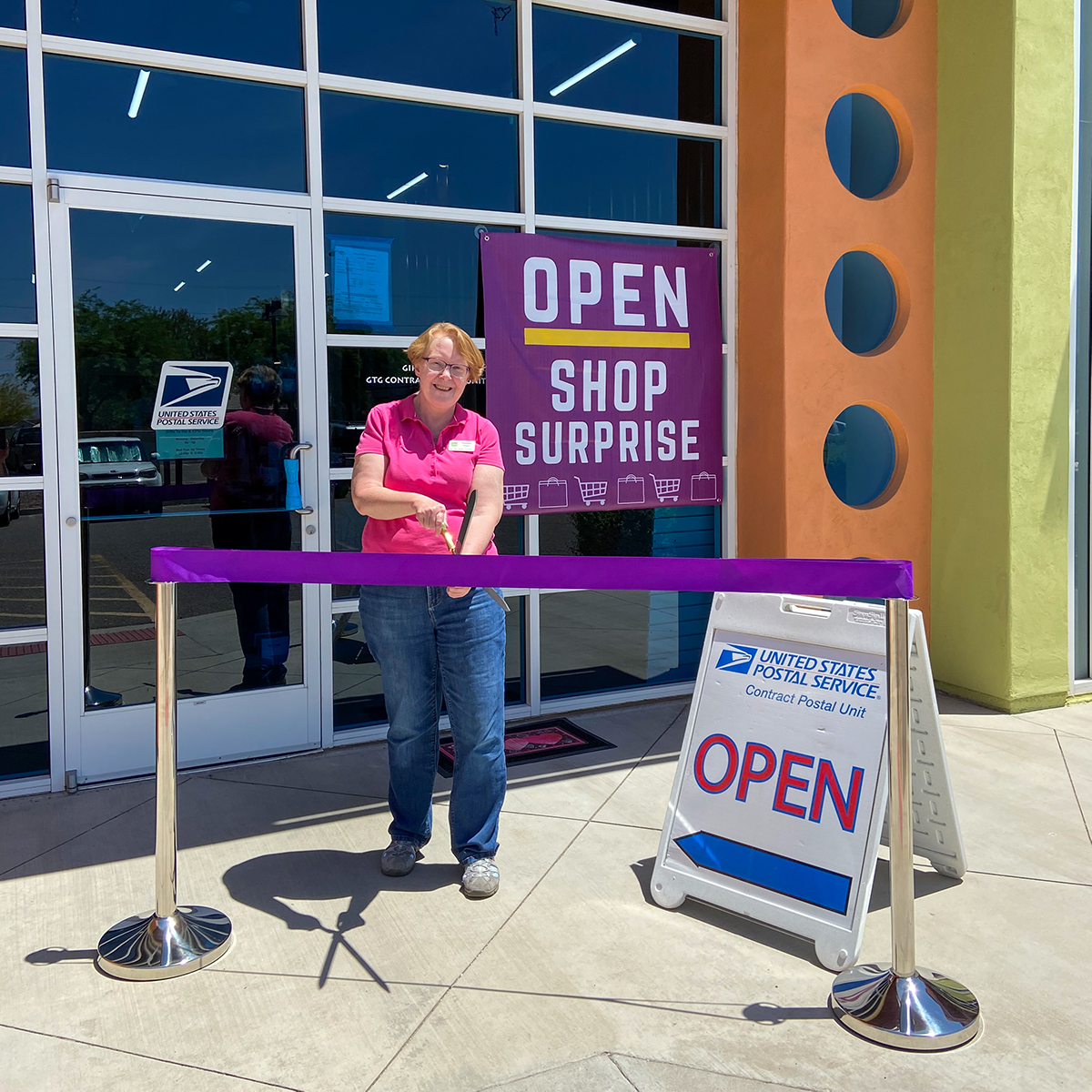 A purple ribbon is cut outside of Gifts to Go for the business' re-opening.