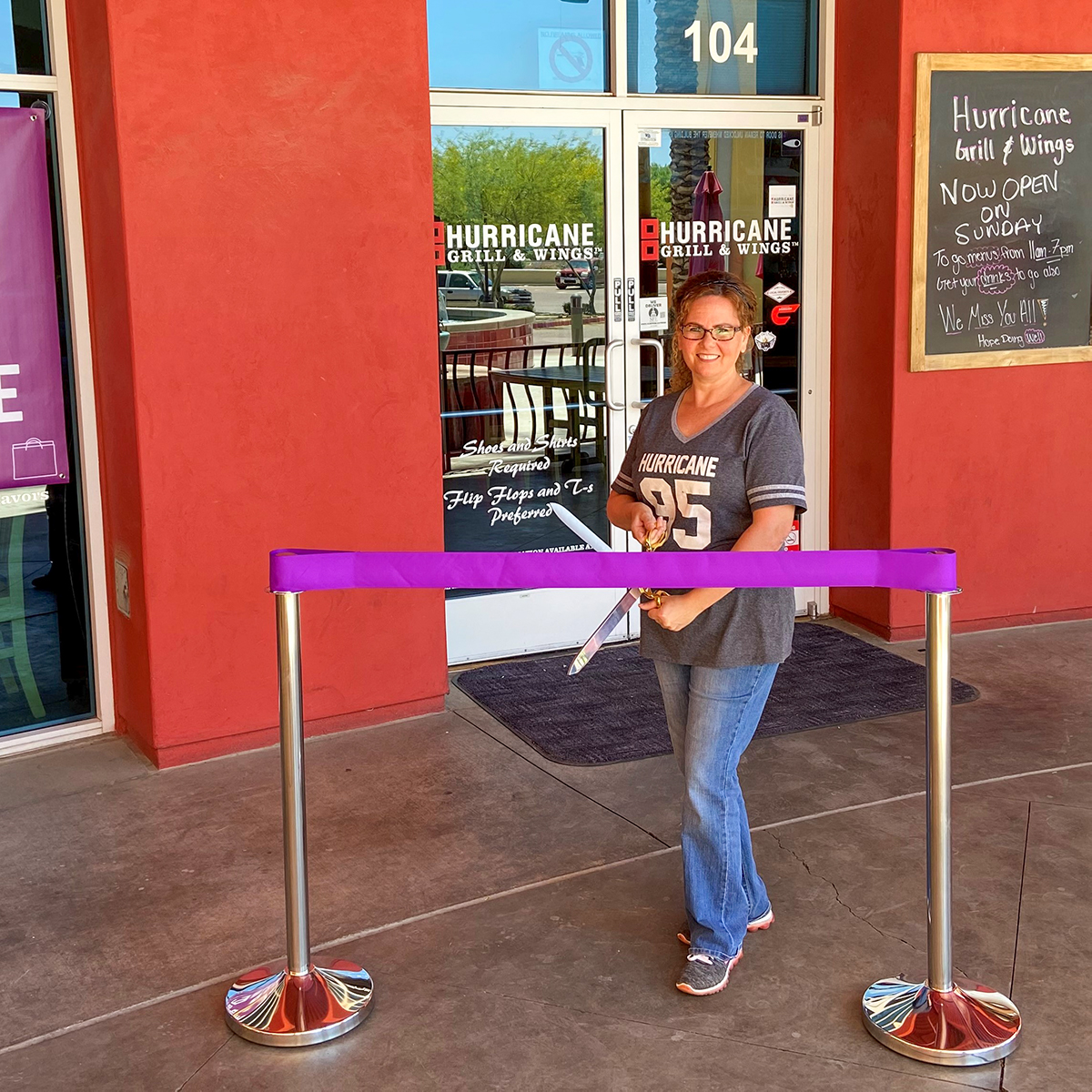 A purple ribbon is cut outside of Hurricane Grill & Wings for the business' re-opening.