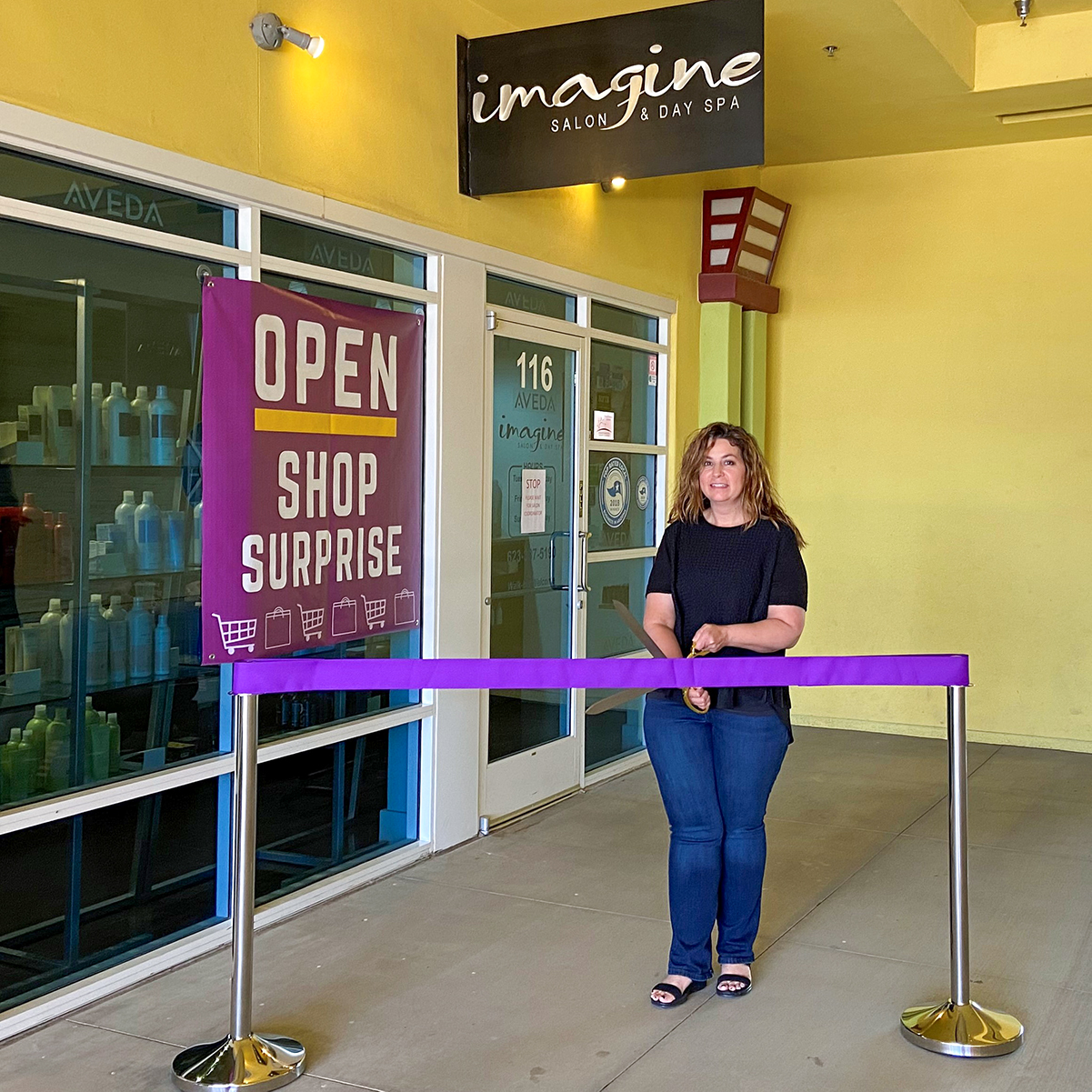 A purple ribbon is cut outside of Imagine Salon & Day Spa for the business' re-opening.
