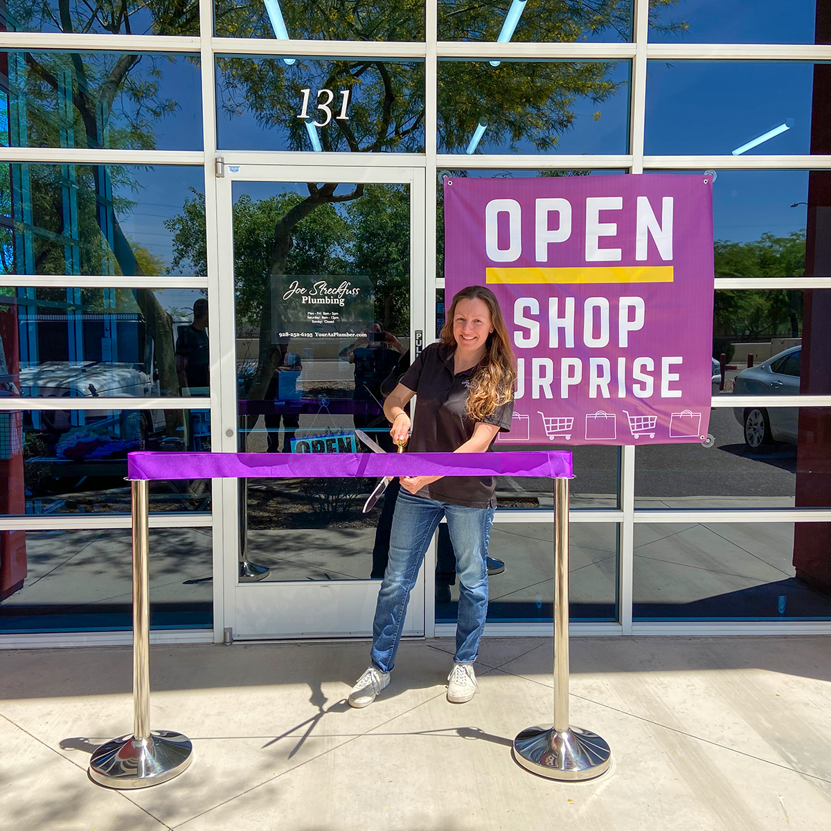 A purple ribbon is cut outside of Joe Streckfuss Plumbing for the business' re-opening.