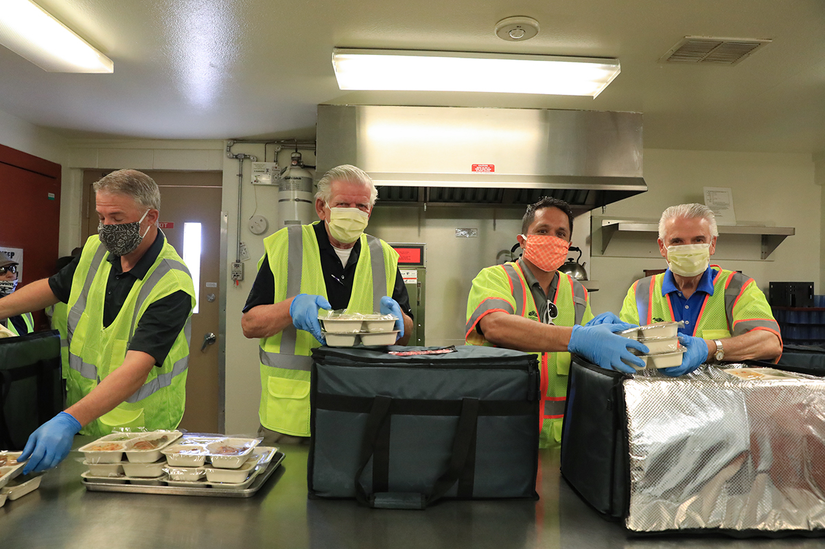 Councilmember Remley, Councilmember Sanders and Mayor Hall pack hot lunches in an insulated bag.