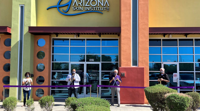 Councilmember Remley, Mayor Hall and Arizona Skin Institute staff hold ribbon cutting scissors outside the businesses new office location.