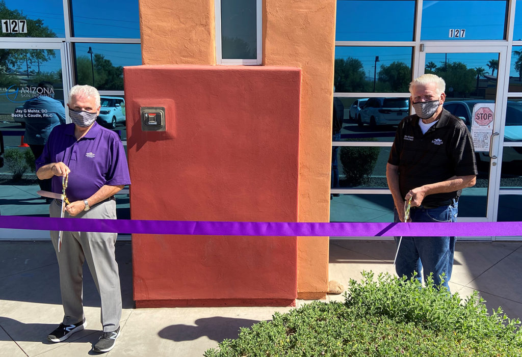 Mayor Hall and Councilmember Remley prepare to cut a purple ribbon at Arizona Skin Institutes new office location.