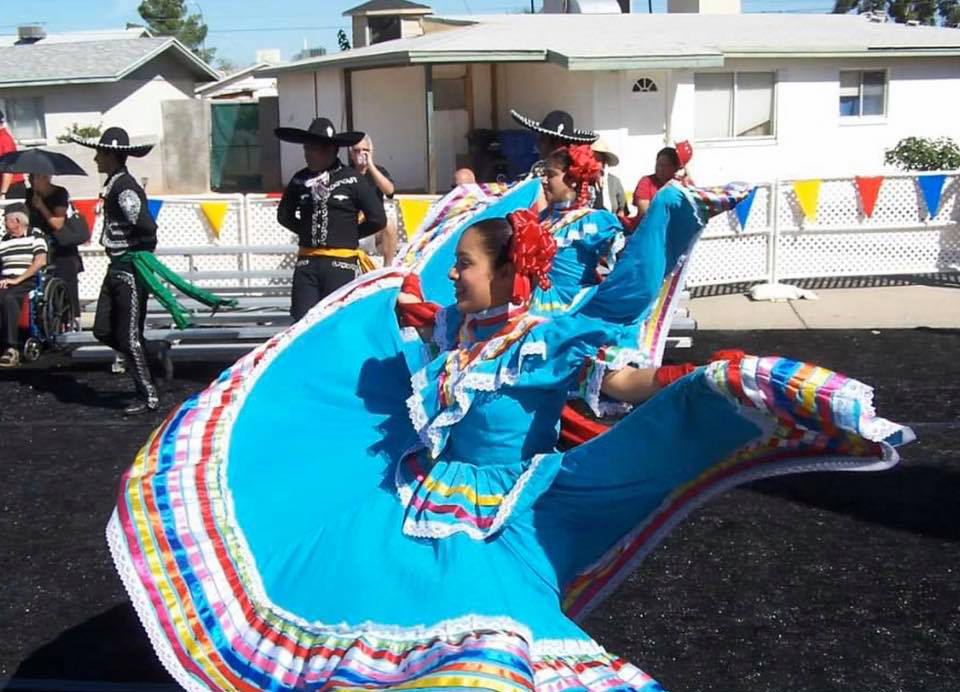 A Folklorico dancer twirls her blue dress.