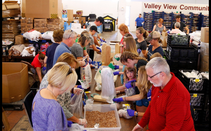 Volunteers fill bags of beans.