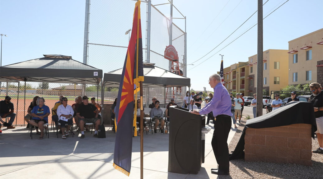 A speaker at a podium talks to guests at the Floyd Gaines ball park ceremony.